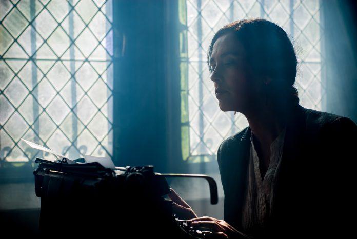 Ghost writer con antica macchina da scrivere.