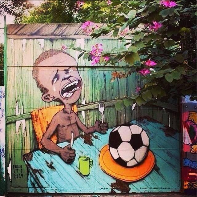 Brasile mondiali 2014: artista di strada dipinge un murales con un bambino che muore di fame e deve mangiare un pallone